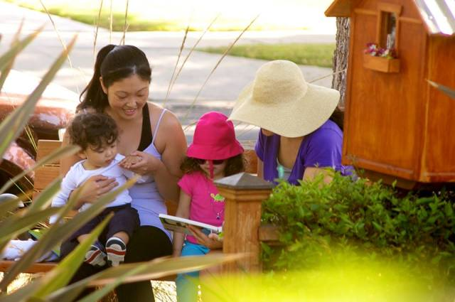 A group of mothers and children gathers to read at the Library.